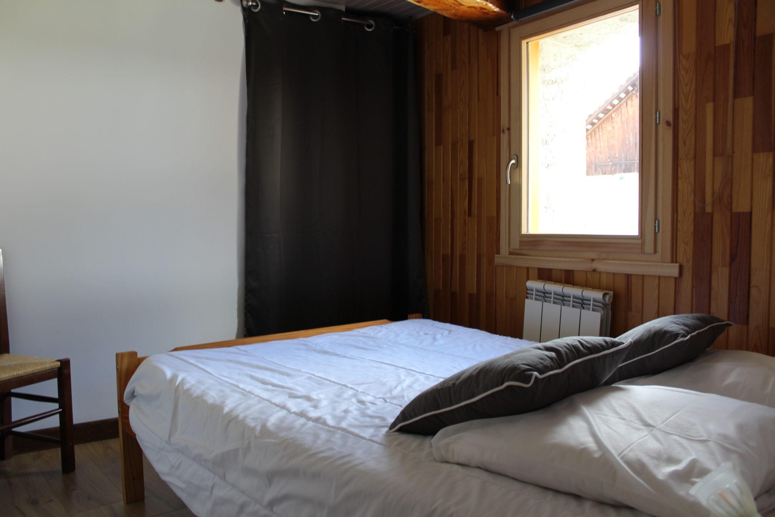 Photo d'un lit, avec coussins et couettes. Fenetre lumineuse en face.