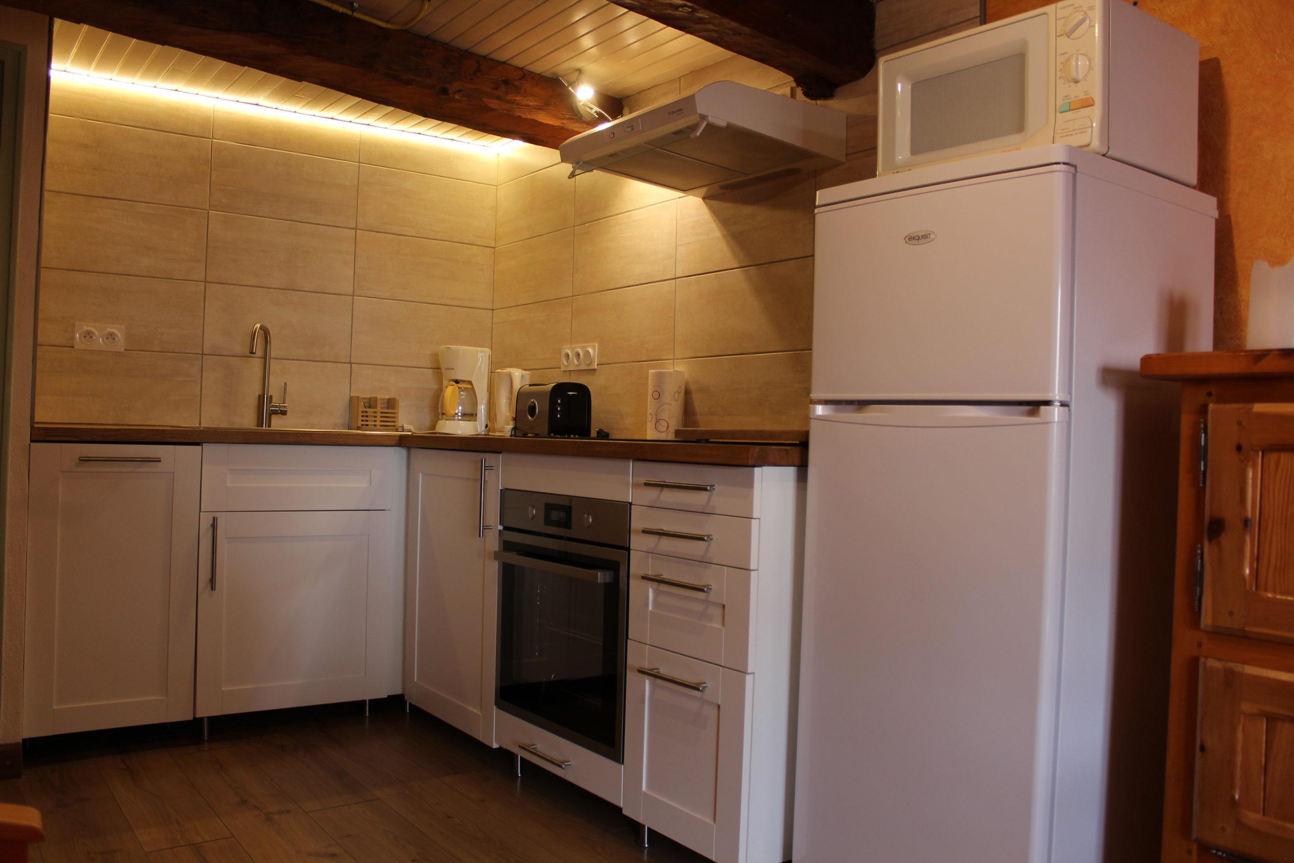 Cuisine blanche avec frigo au premier plan